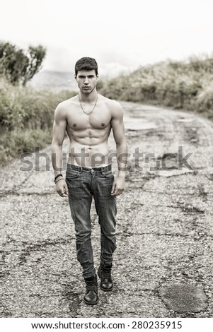 Shirtless sexy muscular young man in jeans walking along rural road in filtered, unsaturated photo - stock photo