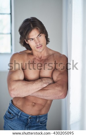 Shirtless suntanned muscular male in denim jeans posing in natural day light.