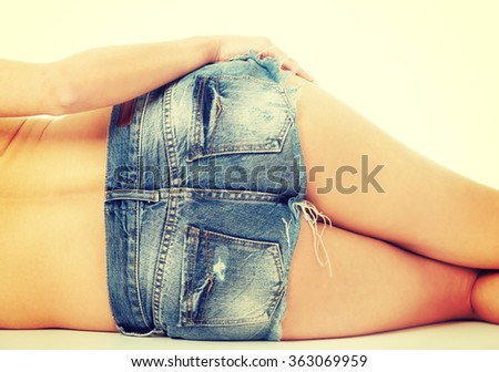 Shirtless woman lying in jeans shorts. - stock photo