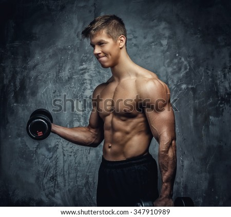 Shirtless young bodybuilder doing exercises with dumbells over grey background.