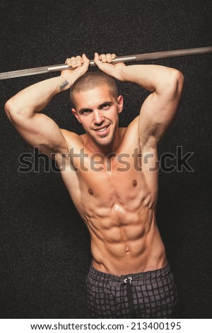 Shirtless young fit man in gym posing and smiling. Fit slim muscular guy posing. Male model with abdominal muscles against black background. Color filter applied. - stock photo