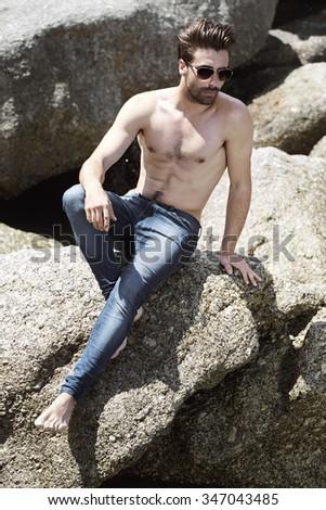 Shirtless young man posing on rock, looking away - stock photo