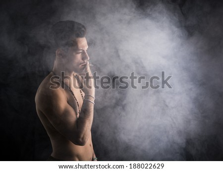 Shirtless young man smoking cigarette with a lot of smoke around him on dark background