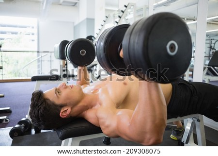 Shirtless young muscular man exercising with dumbbells in gym