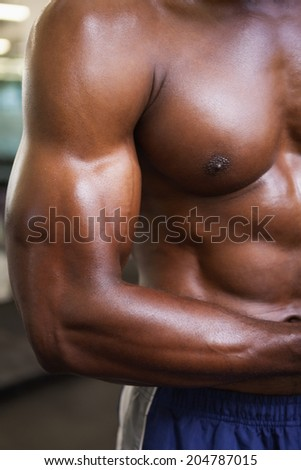 Shirtless young muscular man flexing muscles in gym