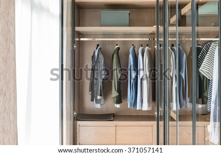 shirts and suite hanging on rail in wooden wardrobe at home