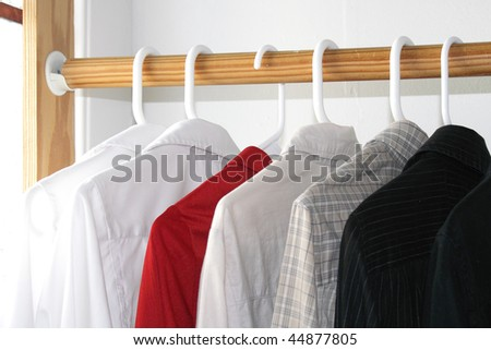 Shirts of different colors in the closet - stock photo
