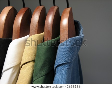 Shirts of different colors on wooden hangers