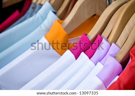 Shirts with brightly colored collars hanging on wooden clothes hangers - stock photo