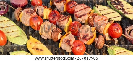 Shish Kabobs BBQ with Meat, Peppers, Tomatoes and Mushrooms With Grilled Vegetables   Zucchine, Eggplant and Onions on Hot Grill. Snack For Summer Barbecue Outdoor Party. - stock photo