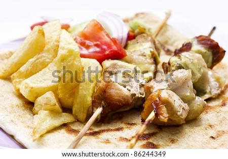 shish kebab(greek souvlaki) with fried potato and salad - stock photo