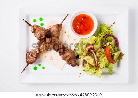 Shish kebab on a skewer lies on a pita. Near sauce and fresh vegetable salad. White background (top view) - stock photo