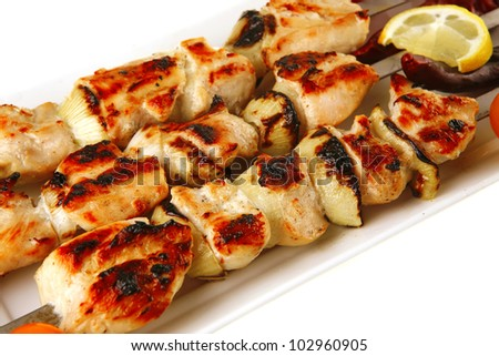 shish kebab on white platter with vegetables - stock photo