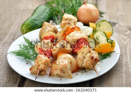 Shish kebab with chicken meat and vegetables on rustic table - stock photo