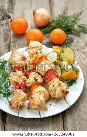 Shish kebab with chicken meat and vegetables on skewers on rustic table - stock photo