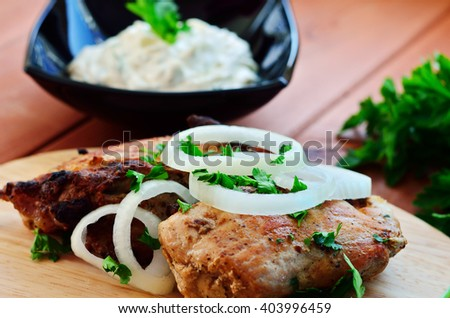 Shish kebab with onion and parsley. White sauce and greens bunch on a wooden background next to the meat.
