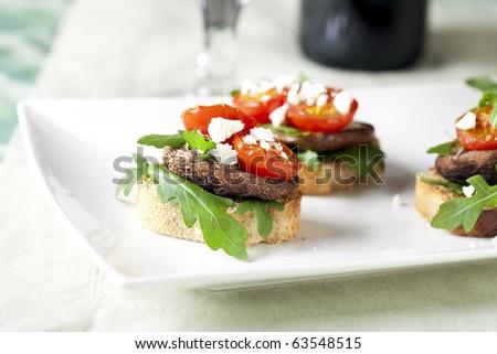 Shitake mushroom tapas with cherry tomatoes and crumbled  feta cheese. - stock photo