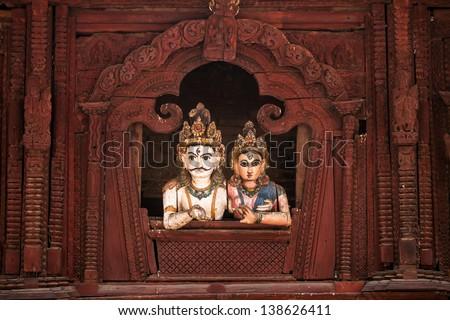Shiva and Parvati wooden figures in the window of Shiva Parvati Hindu temple at Durbar Square in Kathmandu, Nepal - stock photo