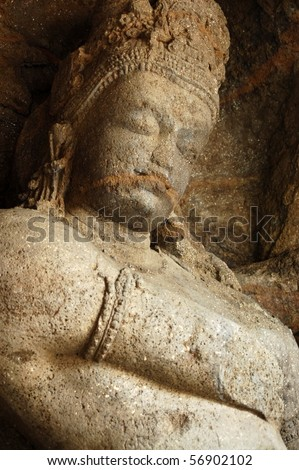 Shiva carving An ancient carving of the Hindu god Shiva.  This huge statue is inside the cave temples on the island of Elephanta off the coast of Mumbai (formerly Bombay), India. - stock photo