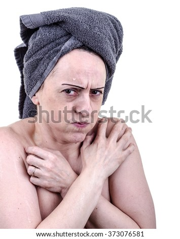 Shivering woman covered in cold water after leaving shower due to lack of hot water. Portrait on White background  - stock photo