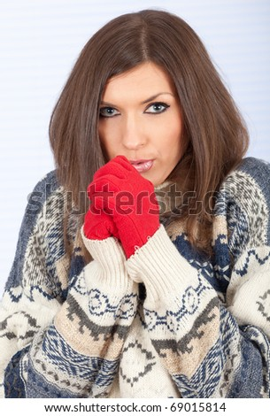 shivering young woman in warm, winter sweater and red mittens - stock photo