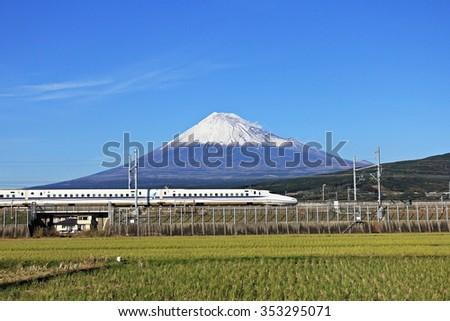 SHIZUOKA,JAPAN - DECEMBER 5,2015 : The Tokaido Shinkansen bullet train passes below Mt. Fuji in Shizuoka Japan. - stock photo