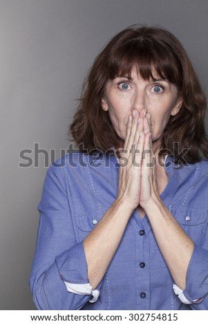 shock and fear concept - beautiful mature woman hiding her face with her hands looking anxious and stressed out with eyes wide opened,closeup in studio shot - stock photo