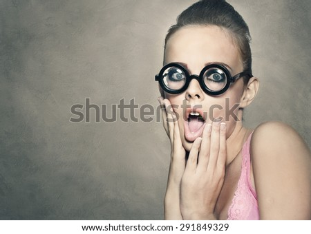 Shock grimace of young pretty woman in funny round glasses on grey background - stock photo