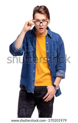 Shock! Studio portrait of amazed young man  holding eyeglasses. Isolated on white. - stock photo