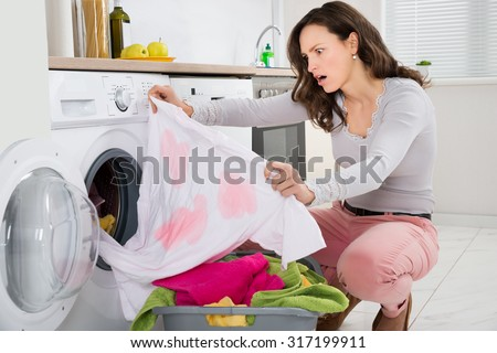 Shock Young Woman Looking At Stained Cloth In Kitchen - stock photo