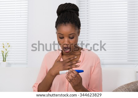 Shocked African Woman Holding Pregnancy Test Kit - stock photo