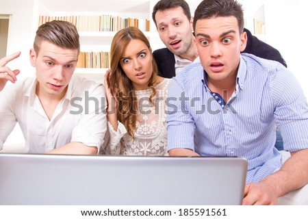 shocked and frustrated casual group of friends sitting on couch looking at laptop, pissed off friends because results, cheering on computer - stock photo