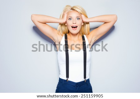 Shocked and happy. Surprised young woman holding hands in hair and staring at camera while standing against grey background   - stock photo
