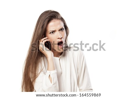 shocked and nervous young woman talking phone - stock photo