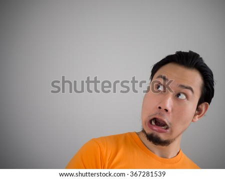 Shocked and surprised face of Asian man looking up to empty space. - stock photo
