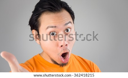 Shocked and surprised face of Asian man show something. - stock photo
