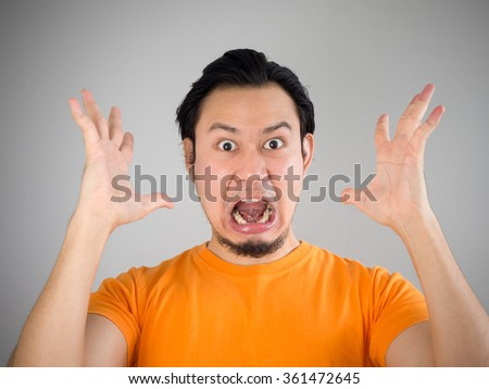 Shocked and surprised face of Asian man with hands up.