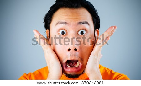 Shocked and surprised face of Asian man with Velvia filter. - stock photo