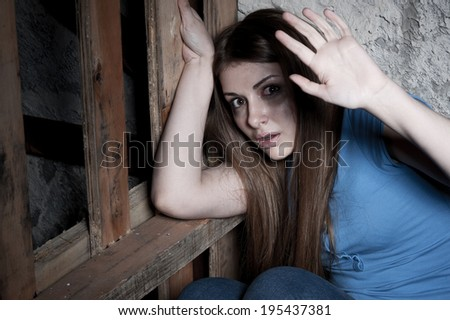 Shocked and terrified. Terrified young woman looking at camera and stretching out hand while leaning at the dark wall - stock photo