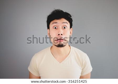 Shocked Asian man in vanilla tshirt. - stock photo