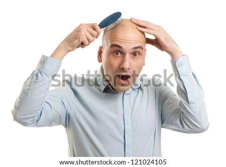 Shocked bald man holding comb - stock photo