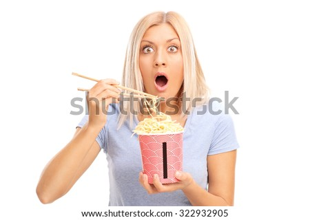 Shocked blond woman eating Chinese noodles and looking at the camera isolated on white background - stock photo