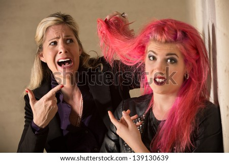 Shocked blond woman holding pink hairdo of teenager - stock photo