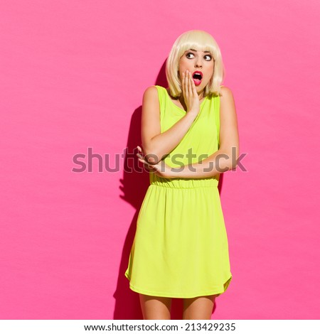 Shocked blonde girl in lime dress lean on the wall. Three quarter length studio shot on pink background. - stock photo