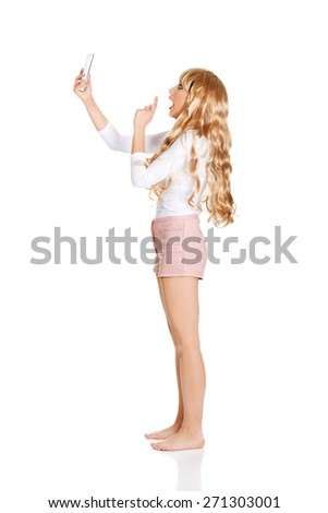 Shocked blonde woman using cellphone. - stock photo