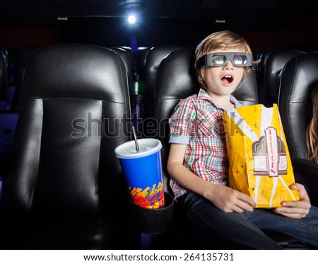 Shocked boy holding snacks while watching 3D movie in cinema theater - stock photo