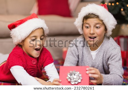 Shocked brother and sister opening a gift at home in the living room