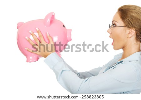 Shocked business woman holding piggy bank. - stock photo