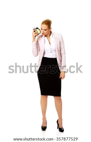 Shocked business woman listening to alarm clock.