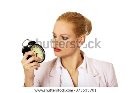 Shocked business woman looking at alarm clock - stock photo